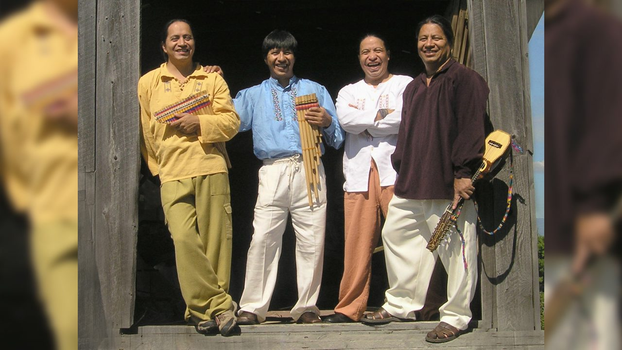Four musicians stand together, smiling.