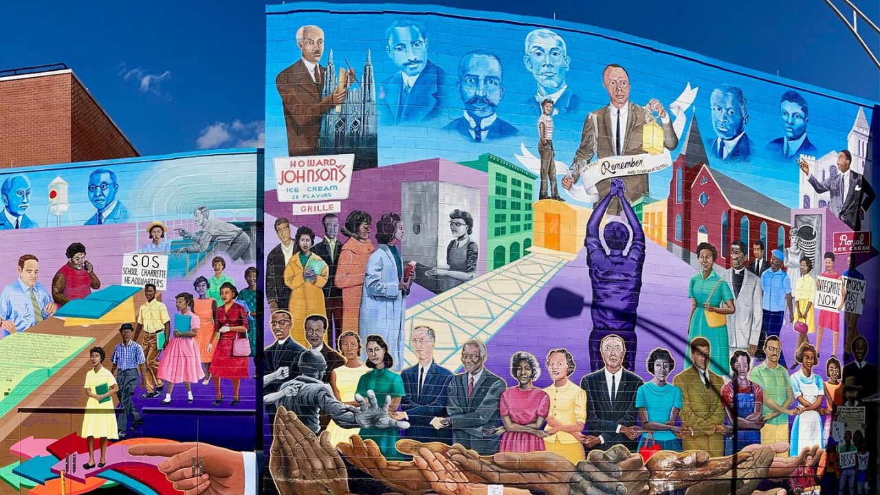 A large mural displays notable Black figures and moments in history.