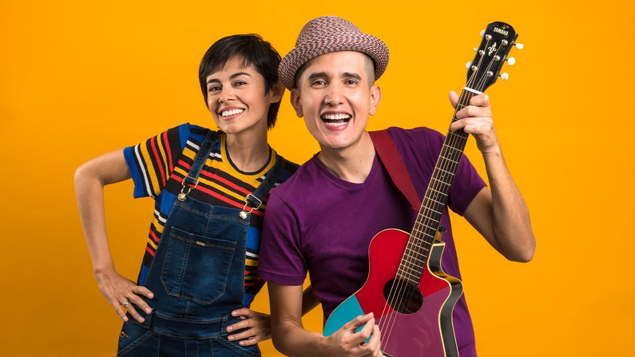 Two smiling musicians stand in front of an orange background.