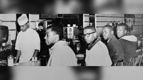A historic photo depicting four Black men sitting at a restaurant counter..