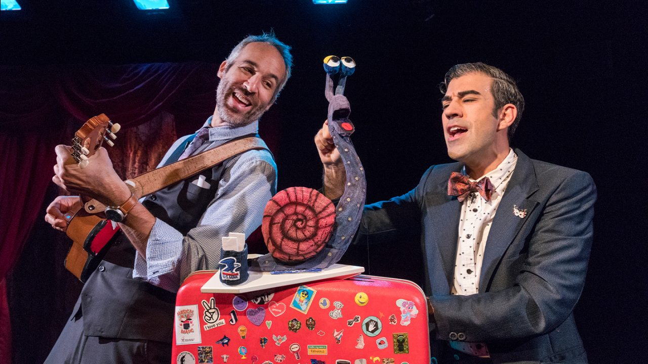 Two men, singing, stand on either side of a snail puppet that sits on a suitcase covered in stickers.
