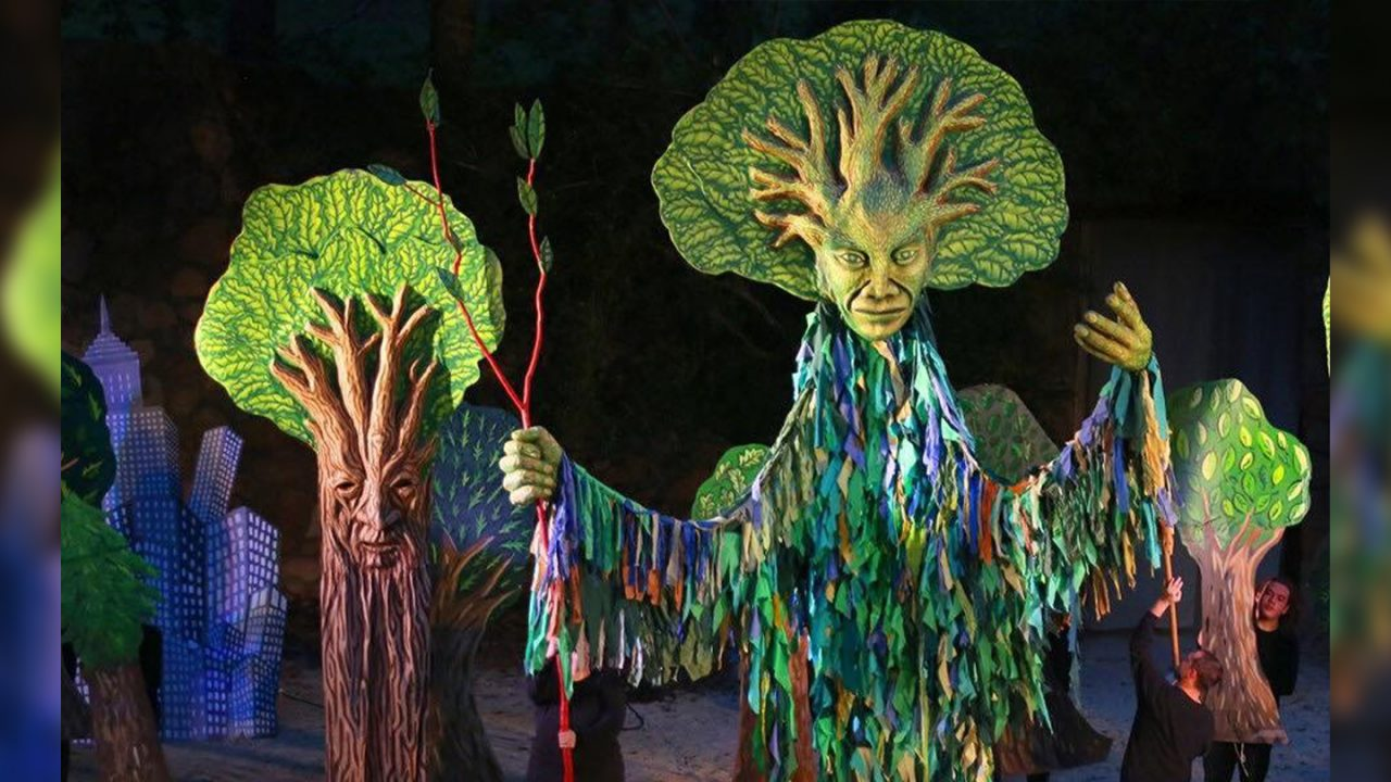 A group of lifesized tree puppets stand in front of a black background.