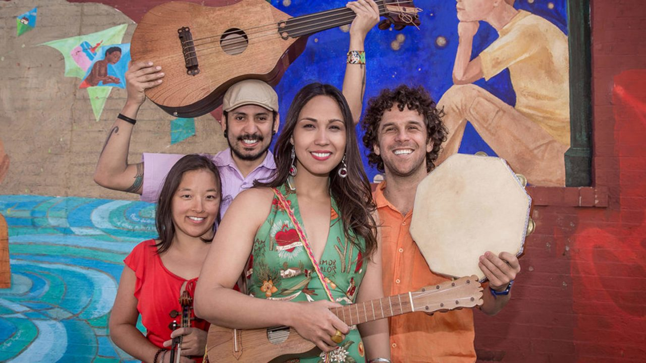 Four smiling musicians stand in front of a mural, holding instruments.