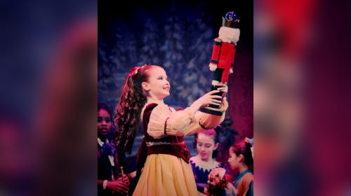 A girl with curly hair dances with her nutcracker doll.